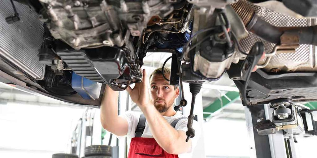 Autoreperatur in der Werkstatt - Auto steht auf einer Hebebühne
